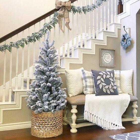 Un ingresso decorato con un pissolo albero, ghirlande tessuti nei toni del bianco e del blu