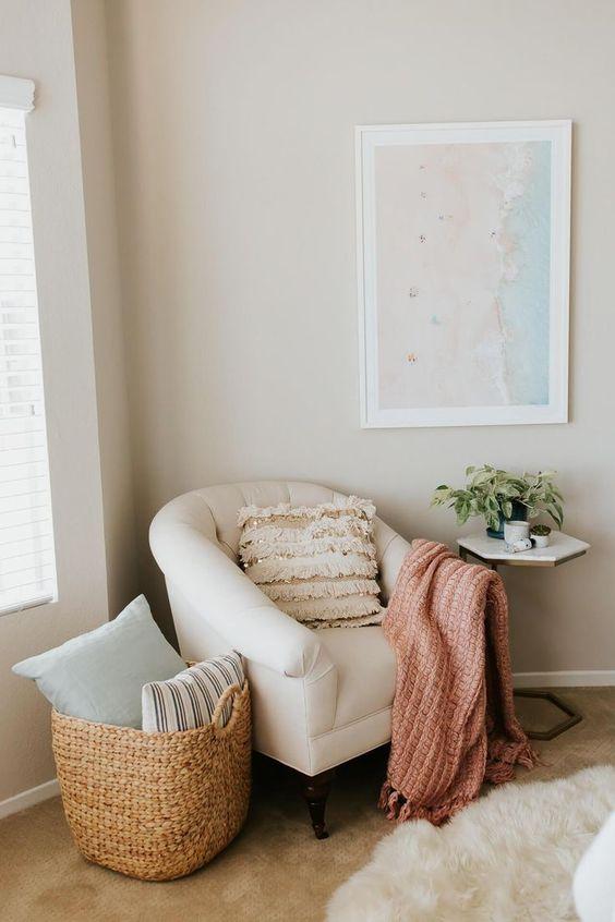 Un angolo relax con una poltrona e un cesto per riporre i cuscini