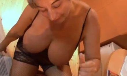 Oma in lingerie, grote hangtieten, wordt op het bureau geneukt
