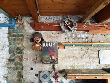 "A wall with some random memorabilia in a ruin bar. There's a poster which says ""Budapest waiting for you"" and a model of a head with a military helmet on it."