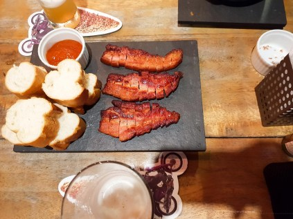 3 sliced perfect pieces of smoked bacon with some bread on the side.