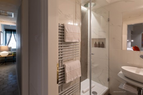 Rain shower with light marble tiles. Appropriately luxurious-looking bathroom.