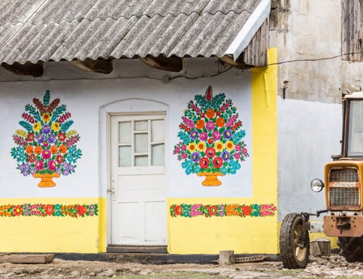 A barn house painted white, with a yellow lower half and huge flowery bouquets on both sides of the main door. There's also an old tractor peeking out from around the corner.