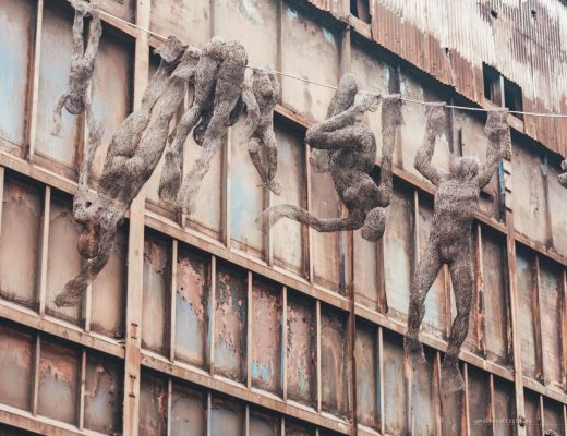 rusty wall of the Dolni Vitkovice complex with human-shaped sculptures made of wire hanging in front of it