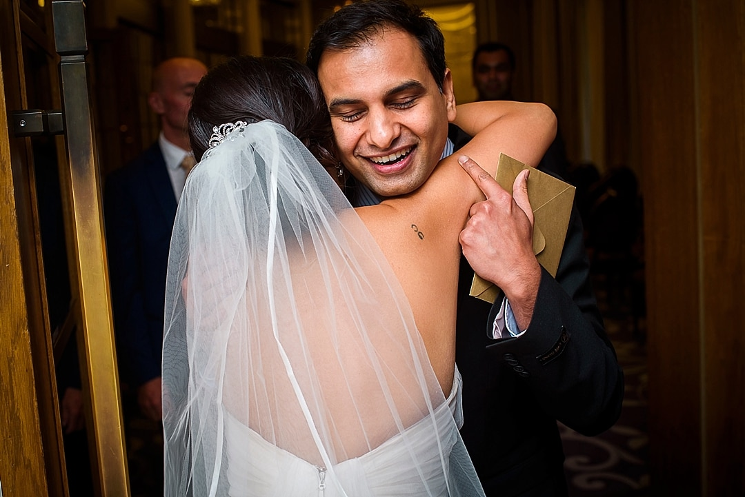 Corinthia Hotel Wedding Photographer hugging the bride