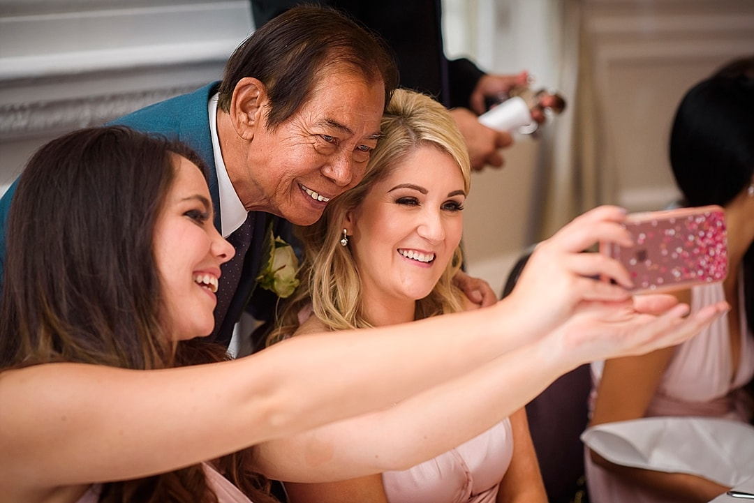 Corinthia Hotel Wedding Photographer Bridesmaids and father of the bride taking selfie