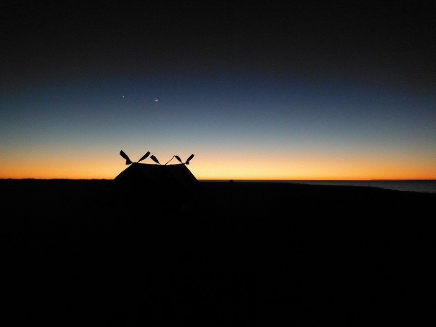 The sun just rising on the horizon, the moon and a single star hovering above the makeshift tent we built on the desert island.