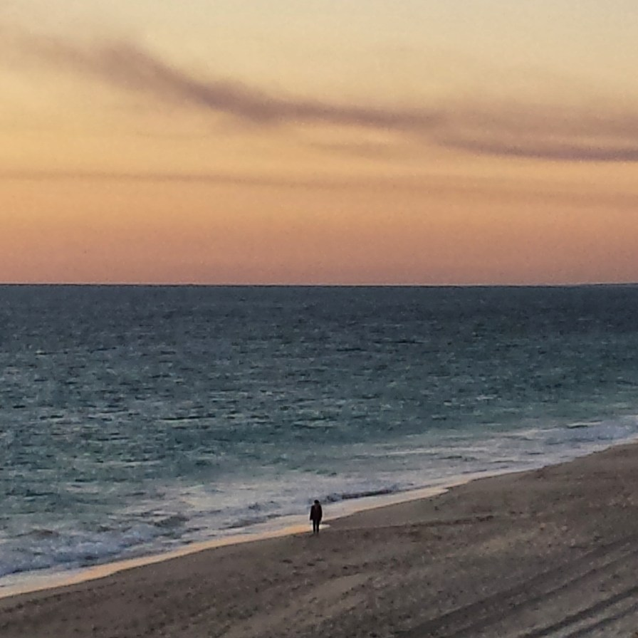 This lone figure strolls along the beach in Fremantle, Western Australia at dusk just as I was photographing the sunset.