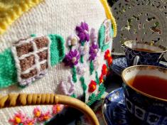 This knitted tea cosy keeps the pot warm in the garden on this crisp spring morning