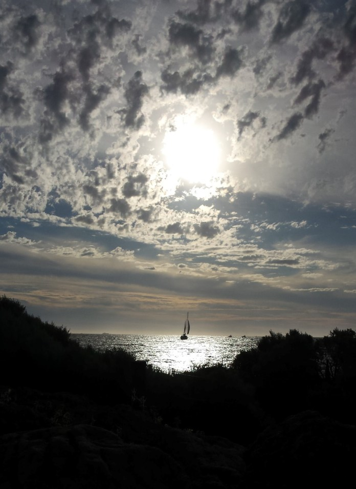 This little sailing craft travels towards the setting sun.