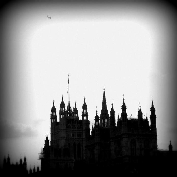 A plane flies above the Gothic spires of the British House of Parliament