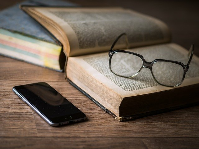 smart phone, glasses on open book