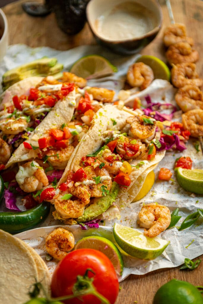 Cajun rubbed grilled shrimp tacos in tortillas with red and green cabbage slaw, a drizzle of crema, pico de gallo and limes around to squeeze on top