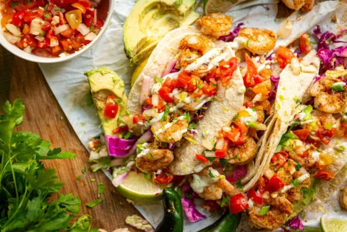 Is there anything better than grilled shrimp tacos? nope. But add a quick tangy slaw and some easy crema and it's pretty much heaven.