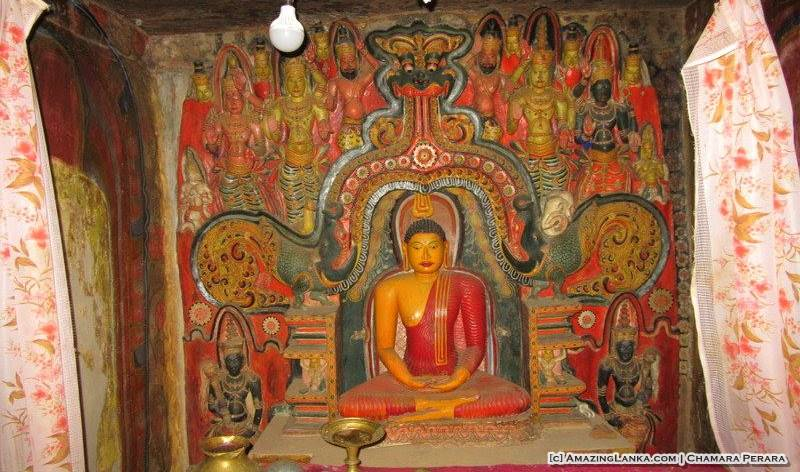 The seated Buddha under a detailed dragon arch at the Dembawa Purana Tampita Viharaya