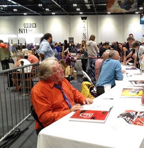 Chris Foss at the LonCon3 art show, signing copies of his newest art book for a long line of fans