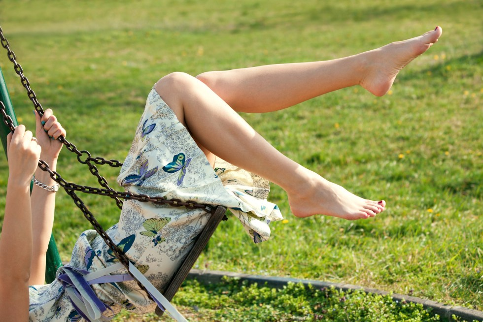barefoot young woman in dress on swing outdoor in park warm spri