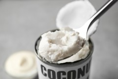 Coconut cream in spoon on grey background