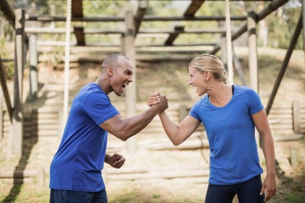 Fit man and woman greeting each other during obstacle course in