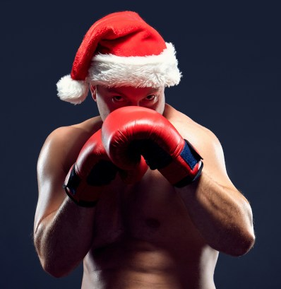 Christmas fitness boxer wearing santa hat boxing on black backgr