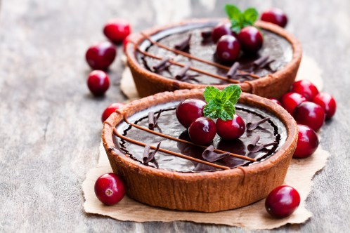 mini chocolate tarts with cranberries on wooden background
