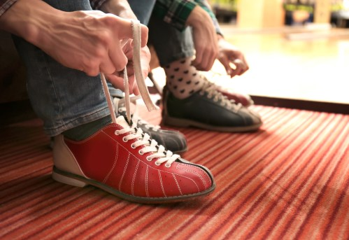 Friends lacing their shoes in bowling club
