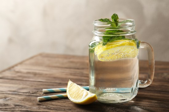 Refreshing lemon water in glass mason jar on wooden table
