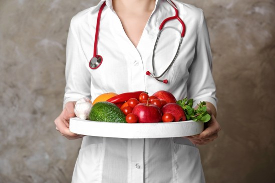 Doctor holding tray with heart healthy foods on color background