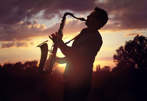 Saxophone player or saxophonist performing sax against sunset