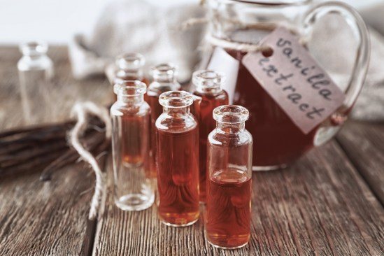 Small bottles with aromatic vanilla extract on table