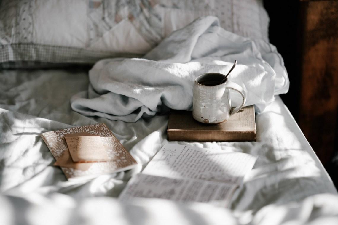 Bett mit Tagebuch und Tee Schlaflosigkeit
