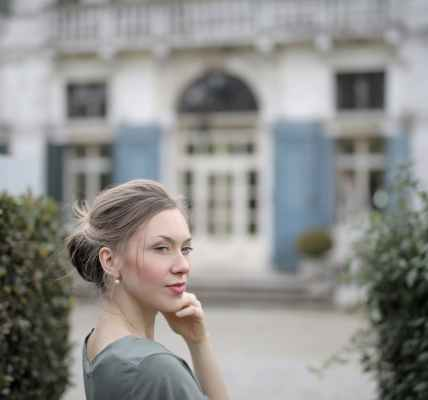 pensive woman on background of old palace among plants
