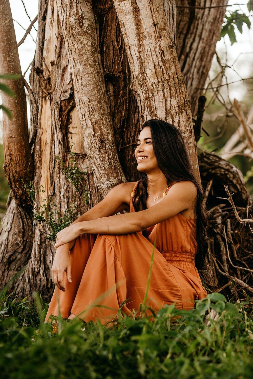 joyful woman in stylish maxi dress resting near old tree