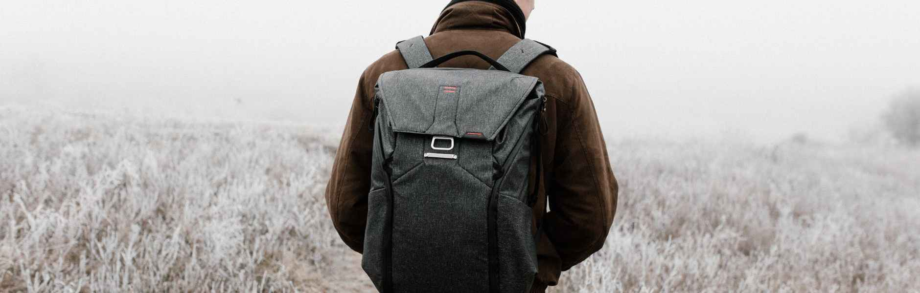 man standing on field carrying a back pack