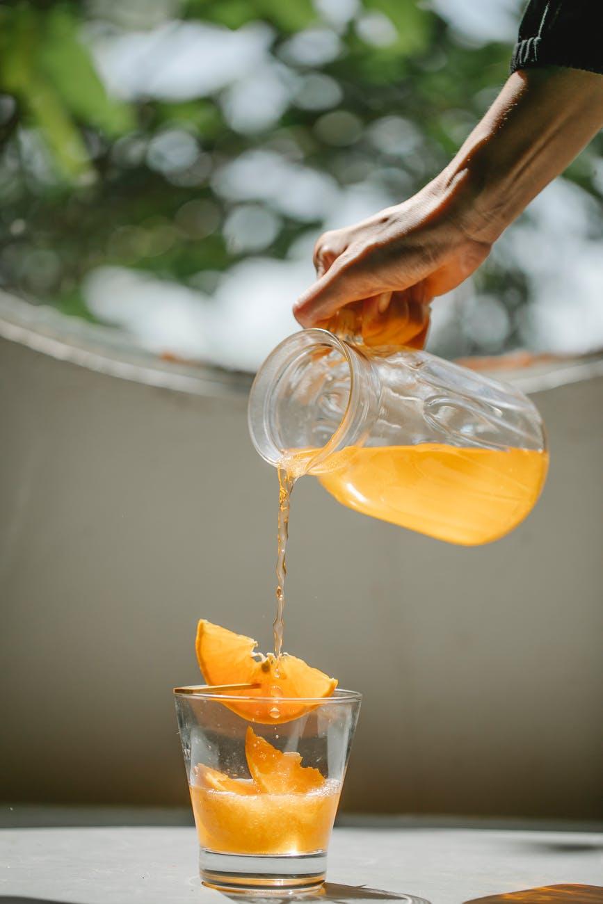 Detoks ili post?  crop woman pouring cold orange beverage into glass