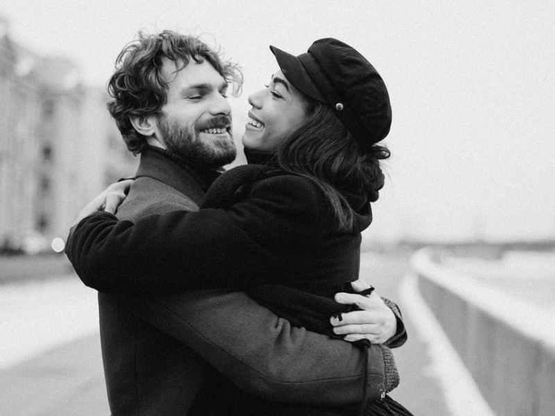 monochrome photo of woman hugging man