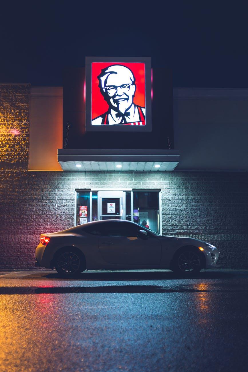 shiny car at drive through cafe at night