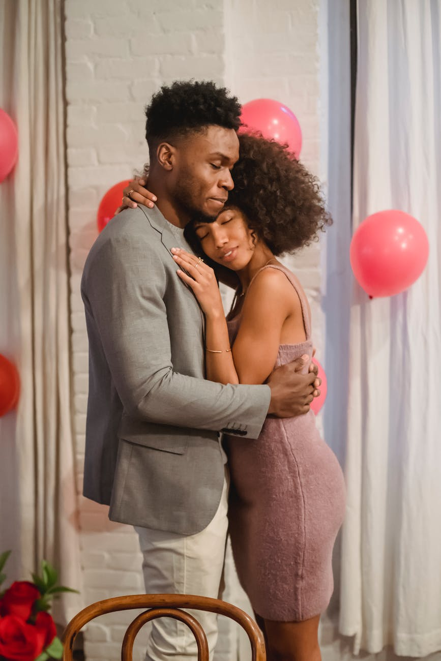 african american couple hugging and dancing in apartment near balloons