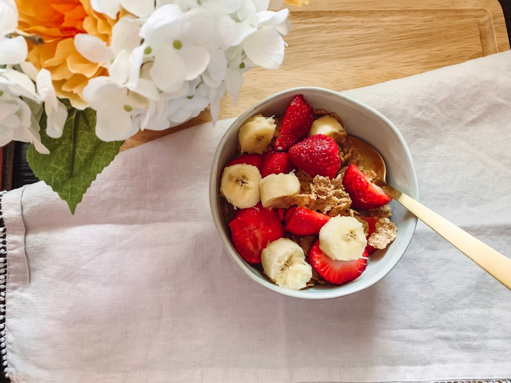 A bowl of special k red berries cereal topped with strawberries and banana.