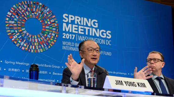 World Bank President Jim Yong Kim gestures as he makes remarks during a press briefing to open the IMF and World Bank's 2017 Annual Spring Meetings, as press spokesman David Theis listens, in Washington