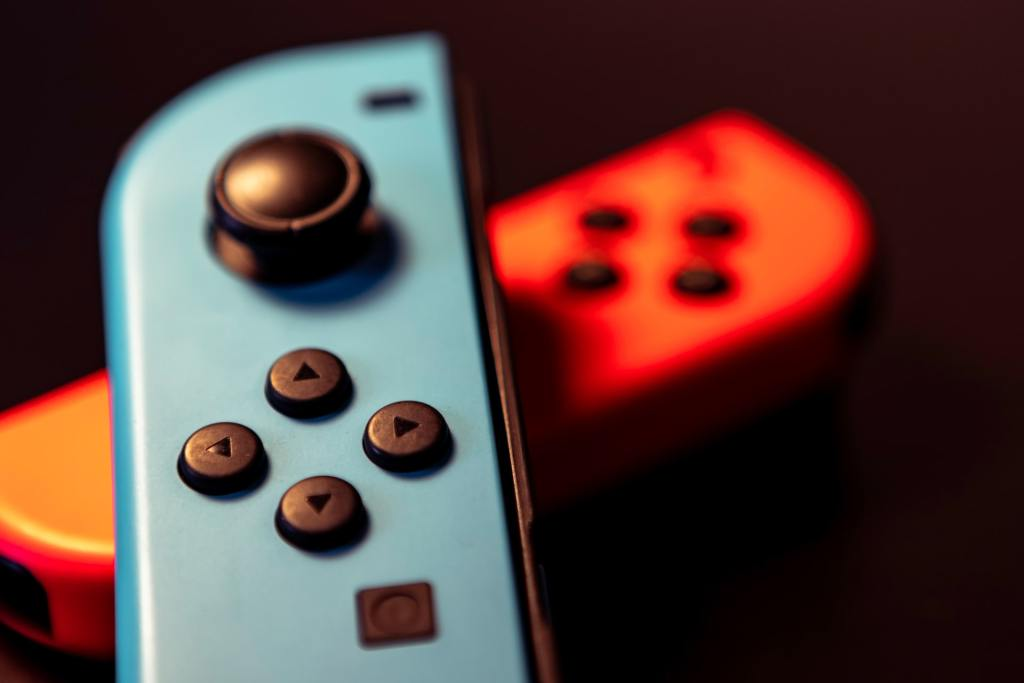 Nintendo switch detached controllers in red and blue over black background