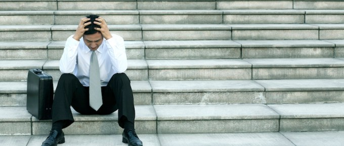 Man on steps with his head in his hands looking distressed.