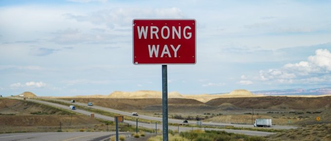 Long empty road with a wrong way sign