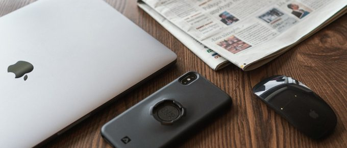 Image of Macbook, phone, mouse, and newspaper