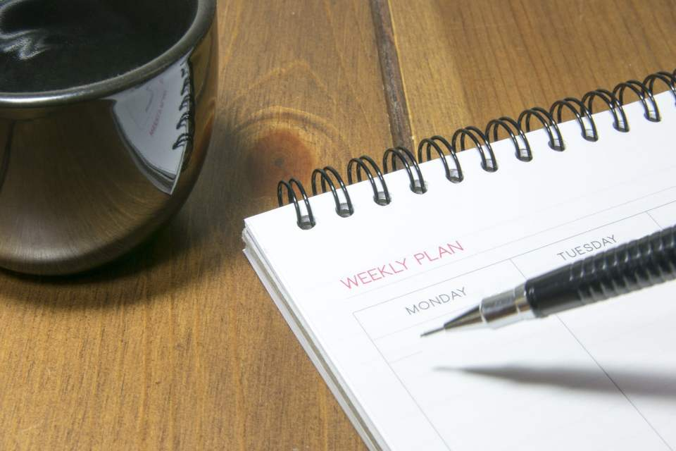 blank weekly planner with a pen poised over the page. A coffee mug is next to it.