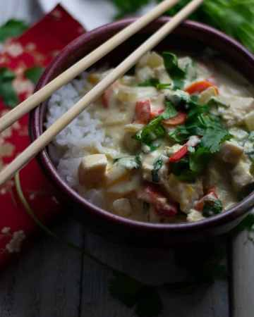 Thai Mahi Mahi Green Coconut Milk Curry in a red bowl with chopsticks on a red napkin