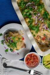 enchilada casserole on white plate and white baking dish with salsa in small dish