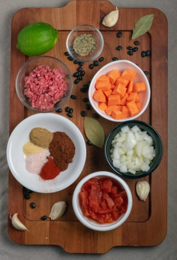 Ingredients for Black Bean Sweet Potato Chili in small bowls on wood tray