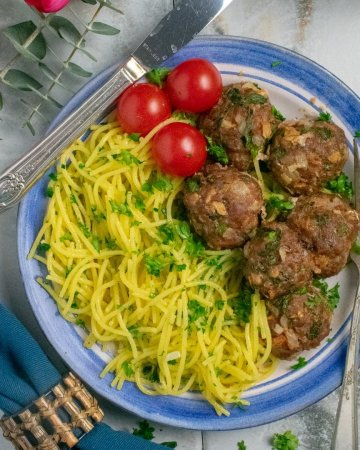 Beef spinach mini-meatloaves and garlic pasta on blue plate with blue napkin sq