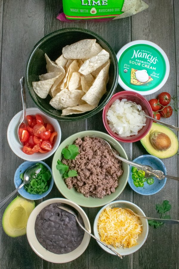 Ingredients for gluten-free nachos in small bowls on table